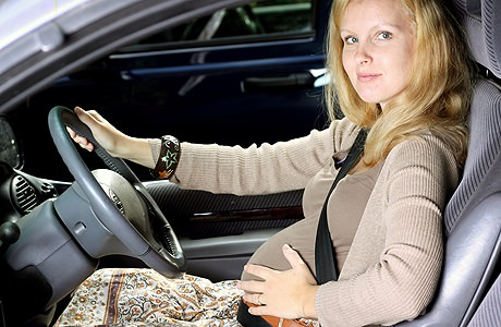 красивая беременная женщина за рулем