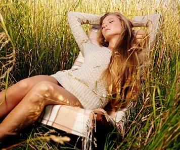 Красивая женщина спит в поле